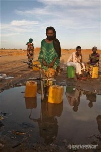 Local women collect water at a water well outside Akokan village. A Greenpeace team is visiting the area searching for dangerous levels of radiation in the cities located close to two uranium mines owned by French company AREVA.